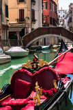 Gondola with Red Seat and Golden Decoration in Typical Canal in Stock Photography