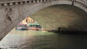 Gondola, Rialto Bridge, Grand Canal, Venice, Italy. Venice, Italy - Gondolier in gondola on Grand Canal under the Rialto Bridge, sightseeing for tourists stock video