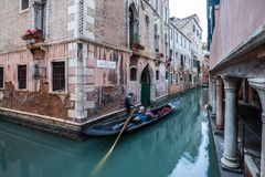 Gondola ride through the canals of Venice. Venetian gondola floating through the narrow canals of Venice`s historic centre Royalty Free Stock Photography