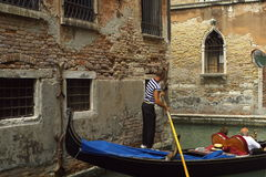 Gondola ride in Venice. Gondolier maneuvering a Venetian gondola with sightseeing passengers in it around a corner in a canal Royalty Free Stock Photos