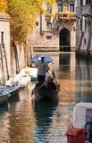 Gondola sails in a canal in autumn day in Venice royalty free stock photo