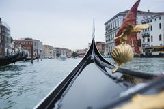 Gondola sails on the canal in Venice. The gondola floats along the canal in Venice. The shell hangs on the gondola. Picture may be used as background for quotes Stock Photos