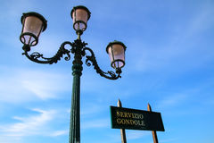 Gondola service sign and street lamp against blue sky near Piazz Stock Image
