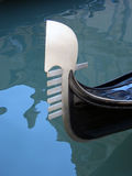 Gondola tail, Venice 03, Italy. Tail of a gondola waiting for customers on Venice canals, shining against the blue water. Gondolas are one of the distinct Royalty Free Stock Photos