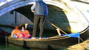 Gondola took passengers passing the bridge in Venice stock video
