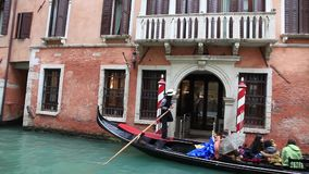 Gondola with Tourist on a Venetian Canal in a Rainy Day. VENICE-MAR 02,2014: A gondola with tourists floating on a canal, in a rainy day, in Venice on March 2 stock footage