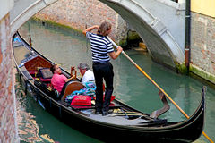 Gondola with tourists and gondolier in Venice, Italy Stock Image