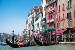 Gondola with tourists in Grand Canal. Venetian long boats gondolas leaving their moorings with tourists on the board in Grand Canal at a bright sunny day - 18 Stock Photos