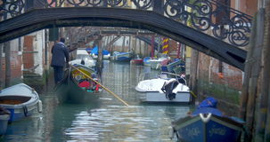 Gondola with tourists sailing on Venetian canal stock video footage