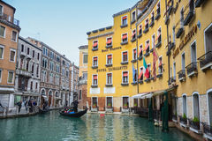 Gondola with tourists sailing in water canal. VENICE, ITALY - FEBRUARY 15 : Tourists  sightseeing and sailing in a gondola through a water canal next to Hotel Stock Photo