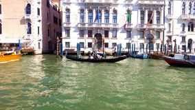 A gondola transports its passengers through a canal in Venice. stock photography