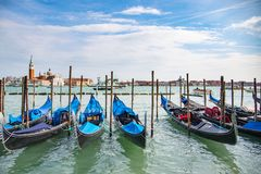 Gondola in Venice. The beautiful view of traditional Gondola boat on canal with historic Basilica di Santa Maria della Salute in the background on a sunny day Royalty Free Stock Photo
