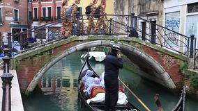 Gondola in Venice. VENICE-MAR 02,2014:A gondola with tourists floating under a traditional bridge in Venice on March 2, 2014. Venice is one of the most popular stock video footage