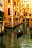 Gondola in Venice. A gondola with tourists going down a small canal lined with urban houses Stock Photos