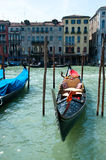 Gondola on water. Traditional boat gondola with bright and attractive luxury seat wallowing on the waves against the view on old houses near the water - 18 May Royalty Free Stock Images