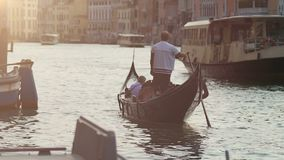 Gondola and water taxi going down channel carrying people onboard, slow motion. Stock footage stock video footage
