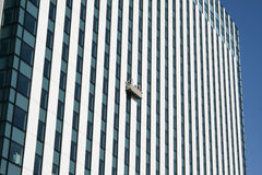 Gondola with window cleaners on skyscraper Royalty Free Stock Image
