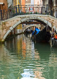 Gondolas. Narrow Venetian canal with gondolas and reflections, Italy Stock Image