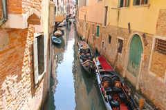 Gondolas and boats in a narrow canal in Venice Stock Photo