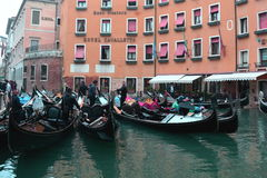 Gondolas and Buildings in Venice,Italy. Gondoliers and their gondolas gather here for good conversation and hopefully some  eager tourists,to take out and let Stock Images