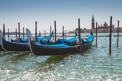 Gondolas docked to the poles on Canal in Venice. Gondolas on Grand Canal against San Giorgio Maggiore church in Venice, Italy Stock Images