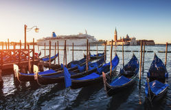 Gondolas on the huge luxury cruise ship. In the Grand Canal in Venice. More than 10 million tourists visit Venice every year Stock Images