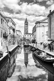 Gondolas moored along water canal in Venice bw Stock Image