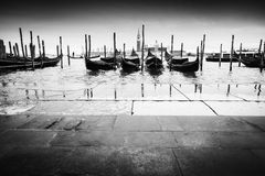 Gondolas moored in front of pavement bw Royalty Free Stock Photos