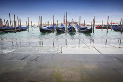 Gondolas moored in front of pavement Stock Images