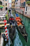 Gondolas moored in a narrow canal in Venice, Italy. Venice is situated across a group of 117 small islands that are separated by canals and linked by bridges stock image