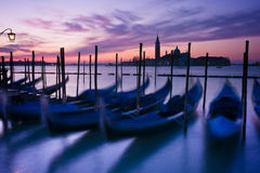 Gondolas moored by Saint Mark's square in Venice. Gondolas moored by Saint Mark's square at dawn with San Giorgio di Maggiore church beyond - Venice, Venezia Royalty Free Stock Photos