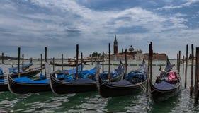 Gondolas moored by Saint Mark square with San Giorgio di Maggiore church in Venice, Italy. royalty free stock photos