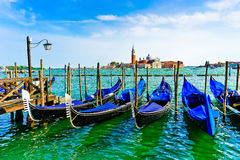 Gondolas moored in Venice. Gondolas moored by St Mark`s Square with Church of San Giorgio Maggiore in the background in Venice Stock Images