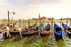 Gondolas moored in Venice. Gondolas moored by St Mark`s Square with Church of San Giorgio Maggiore in the background in Venice Stock Photos