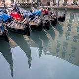 Gondolas parked on a canal in Venice, Italy showing the decorative ferro / iron at the bow of the boats and the risso. Close up of gondolas parked on a canal in Stock Images