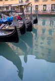 Gondolas parked on a canal in Venice, Italy showing the decorative ferro / iron at the bow of the boats and the risso. Close up of gondolas parked on a canal in Royalty Free Stock Images
