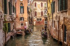 Gondolas with people sail on an old narrow canal in Venice. Venice, Italy - May 20, 2017: Gondolas with people sail on an old narrow canal in Venice. Gondola is stock images