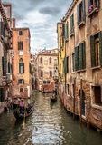 Gondolas with people sail on an old narrow canal in Venice. Venice, Italy - May 20, 2017: Gondolas with people sail on an old narrow canal in Venice. Gondola is royalty free stock images