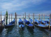 Gondolas at pier under blue sky Stock Photos