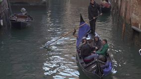 Boat traffic and gondolas at a small canal in Venice stock video footage