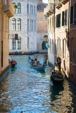 Gondolas with tourists on the Venetian canals, Italy. VENICE, ITALY - SEPTEMBER 25, 2017: Gondolas with tourists on the Venetian canals Stock Photo