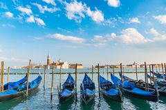 Gondolas in Venice. The beautiful view of traditional Gondola boat on canal with historic Basilica di Santa Maria della Salute in the background on a sunny day Stock Images