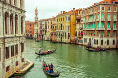 Gondolas in Venice. Grand Canal in Venice with some gondolas and tourists during relaxing trip surrounded by historic architecture of the city Royalty Free Stock Image