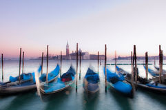 Gondolas in Venice, Italy. Traditional Venetian gondolas moored on the waterfront of Venice, Italy. Captured during sunset with motion blur Stock Photo