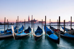 Gondolas in Venice, Italy. Traditional Venetian gondolas moored on the waterfront of Venice, Italy. Captured during sunset with motion blur Stock Images