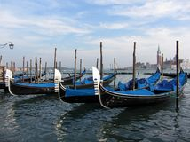 Gondolas Waiting For Hire. Photo of gondolas waiting for tourists at the waterfront in venice italy.  This is next to the doge's palace.  A ride can cost up to $ Stock Image