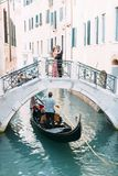Gondole in chanel of Venice, Italy. Lovers hugging and kissing stand on the bridge of the canal.  royalty free stock photography
