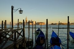 Gondole Stazio Danieliin the warm afternoon light, with Church of San Giorgio Maggiore on the background. Venice, Italy stock images