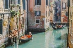 Gondole sul canale stretto e sulla piccola barca legati accanto alla vecchia casa con mattoni a vista rossa con il balcone di leg immagini stock