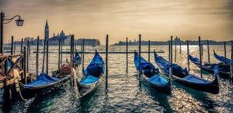 Gondoler i Venedig på solnedgången Arkivbild